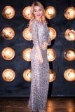 Mulher loura nova bonita em um vestido 'sexy' de prata longo no fundo preto com luzes fotografia de stock