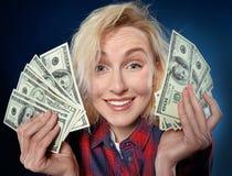 A MULHER loura nova bonita está guardando uma pilha de dinheiro imagens de stock royalty free