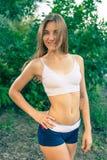 Mulher loura nova bonita na camiseta de alças branca e Foto de Stock