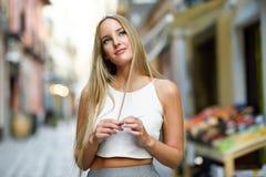 Mulher loura nova bonita no fundo urbano imagem de stock royalty free