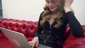 Mulher loura nova bonita no sofá vermelho usando o portátil e comendo uma maçã verde na sala de visitas filme