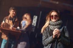 Mulher loura nova bonita nos óculos de sol que guardam o copo e o croissant de café e que olham o sol com smil Fotos de Stock