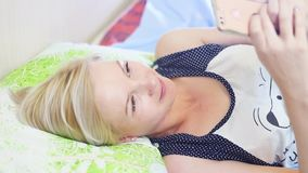 Mulher loura nova bonita que encontra-se na cama e que fala a alguém que usa o smartphone filme