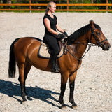 Mulher loura nova bonita que monta um cavalo imagens de stock royalty free