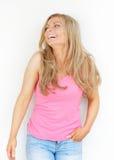 Mulher loura nova bonita que ri e que olha acima Imagem de Stock