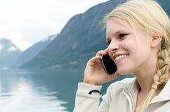 A mulher loura nova chamou acima com seu Smartphone Fotografia de Stock Royalty Free