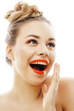 A mulher loura nova com brilhante compõe apontar de sorriso gesticulando emocional isolada como chicotes da boneca no branco Fotos de Stock