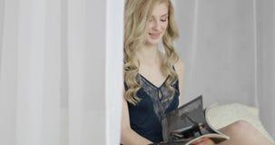 Mulher loura nova com cabelo encaracolado que lê um compartimento vídeos de arquivo