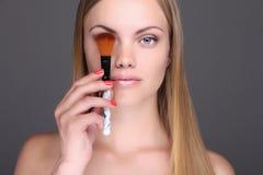 Mulher loura nova com escova da composição Fotografia de Stock