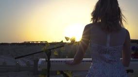 Mulher loura nova com música romântica dos jogos no piano digital no por do sol A menina bonita canta executa na fase com o sol s filme