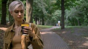 Mulher loura nova com penteado curto que anda no parque e no café bebendo video estoque
