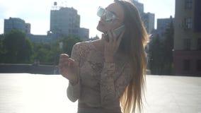 Mulher loura nova da beleza em óculos de sol do espelho que fala o telefone filme