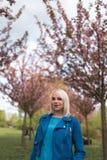 Mulher loura nova da m?e que aprecia o tempo livre - vestido no casaco azul e nas cal?as brancas imagens de stock royalty free