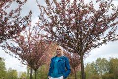 Mulher loura nova da m?e que aprecia o tempo livre - vestido no casaco azul e nas cal?as brancas fotos de stock royalty free