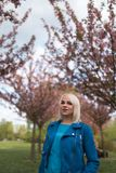 Mulher loura nova da m?e que aprecia o tempo livre - vestido no casaco azul e nas cal?as brancas imagem de stock royalty free