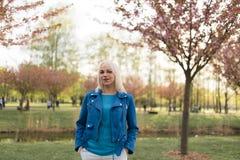 Mulher loura nova da m?e que aprecia o tempo livre - vestido no casaco azul e nas cal?as brancas foto de stock