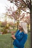 Mulher loura nova da m?e que aprecia o tempo livre - vestido no casaco azul e nas cal?as brancas fotografia de stock royalty free