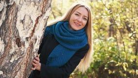 Mulher loura nova de sorriso da beleza no parque colorido do outono no dia ensolarado, apreciando a folha do outono com um sorris vídeos de arquivo