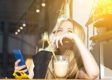 mulher loura nova de sorriso feliz que bebe um latte em um café para um vidro, óculos de sol e telefone no primeiro plano sol da  foto de stock royalty free
