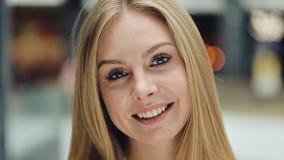 A mulher loura nova de sorriso olha a fixação encantador seu cabelo para uma câmera filme