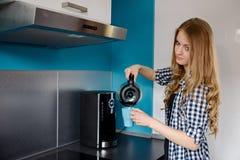 A mulher loura nova derrama o café do fabricante de café em um copo imagens de stock royalty free