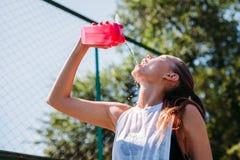 A mulher loura nova desportiva com a garrafa desportiva com água fresca derrama a água nsi mesma no campo de esportes imagens de stock
