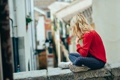 Mulher loura nova do turista que senta-se fora olhando uma rua estreita bonita foto de stock