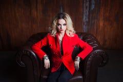 A mulher loura nova e atrativa no revestimento vermelho senta-se na poltrona de couro, parede oxidada do grunge do fundo fotos de stock