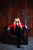 A mulher loura nova e atrativa no revestimento vermelho senta-se na poltrona de couro, parede oxidada do grunge do fundo imagem de stock