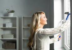 Mulher loura nova e bonita que limpa a janela fotografia de stock