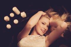 Mulher loura nova em folhas pretas com candels no fundo Imagens de Stock Royalty Free