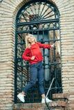 Mulher loura nova feliz ao lado da porta urbana fotos de stock royalty free
