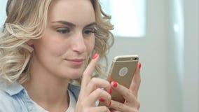 A mulher loura nova feliz está sentando-se em um salão de beleza e está usando-se um smartphone Fotografia de Stock Royalty Free