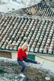 Mulher loura nova feliz que senta-se perto dos telhados bonitos de encantar casas velhas foto de stock royalty free