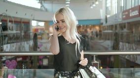 Mulher loura nova feliz que usa o telefone celular em um shopping, compra bonita da menina do estudante na alameda Imagens de Stock Royalty Free