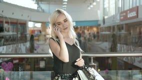 Mulher loura nova feliz que usa o telefone celular em um shopping, compra bonita da menina do estudante na alameda Fotografia de Stock