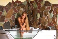 Mulher loura nova na borda do banho Fotografia de Stock