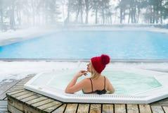 Mulher loura nova na cabana vermelha no Jacuzzi da banheira fora no inverno imagens de stock royalty free