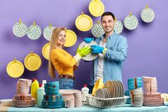 Mulher loura nova na camiseta amarela e no homem moreno que lavam os pratos foto de stock royalty free