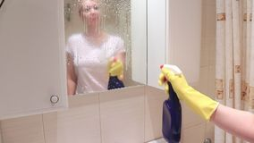 Mulher loura nova nas luvas de borracha amarelas que lavam um espelho do banheiro, polvilhando com o pulverizador do limpador e o filme
