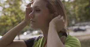 Mulher loura nova no desgaste da aptidão que ajusta o cabelo para treinamento running Dia ensolarado do verão Cidade verde indust filme