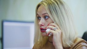Mulher loura nova no escritório que fala no telefone - na frente do computador, monofone com fim do fio acima imagens de stock royalty free