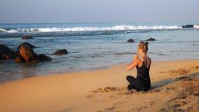 A mulher loura nova no fato de esporte preto medita na pose da ioga video estoque