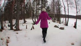 Mulher loura nova no revestimento cor-de-rosa que corre na floresta do inverno video estoque