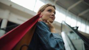 A mulher loura nova no revestimento das calças de brim sorri indo acima nas escadarias moventes no shopping filme