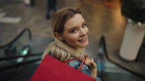 A mulher loura nova no revestimento das calças de brim sorri indo para baixo nas escadarias moventes no shopping video estoque