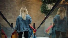 A mulher loura nova no revestimento das calças de brim sorri indo para baixo nas escadarias moventes no shopping vídeos de arquivo