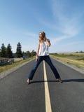 Mulher loura nova no trajeto da bicicleta nas calças de brim Imagem de Stock