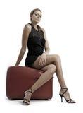 Mulher loura nova no vestido preto que senta-se no pufe Fotografia de Stock Royalty Free