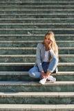 Mulher loura nova pensativa que senta-se em etapas urbanas Imagens de Stock Royalty Free